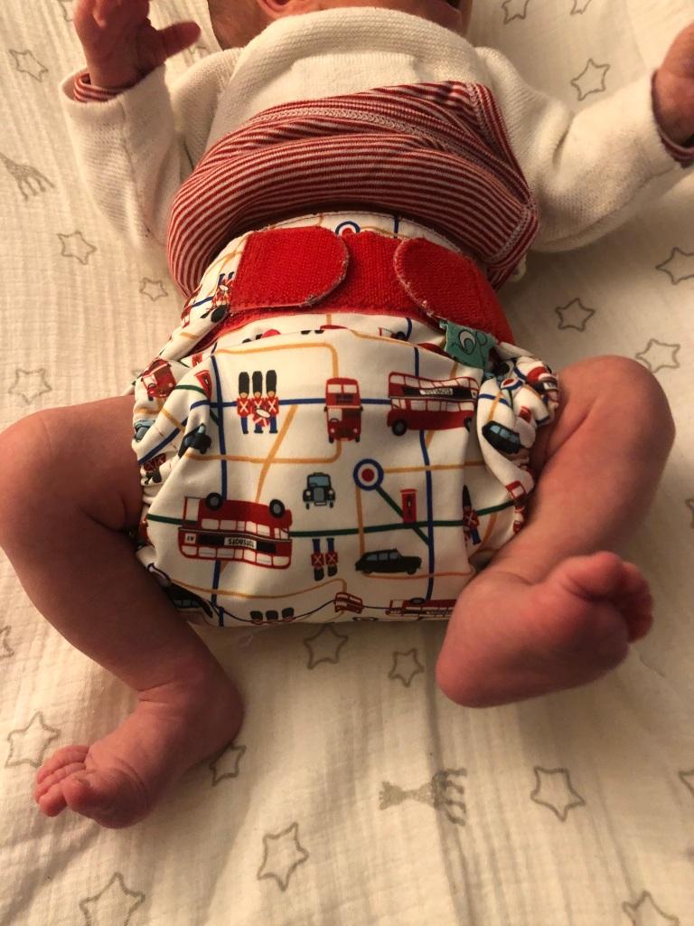 Photo d'un bébé allongé sur le dos avec une couche lavable